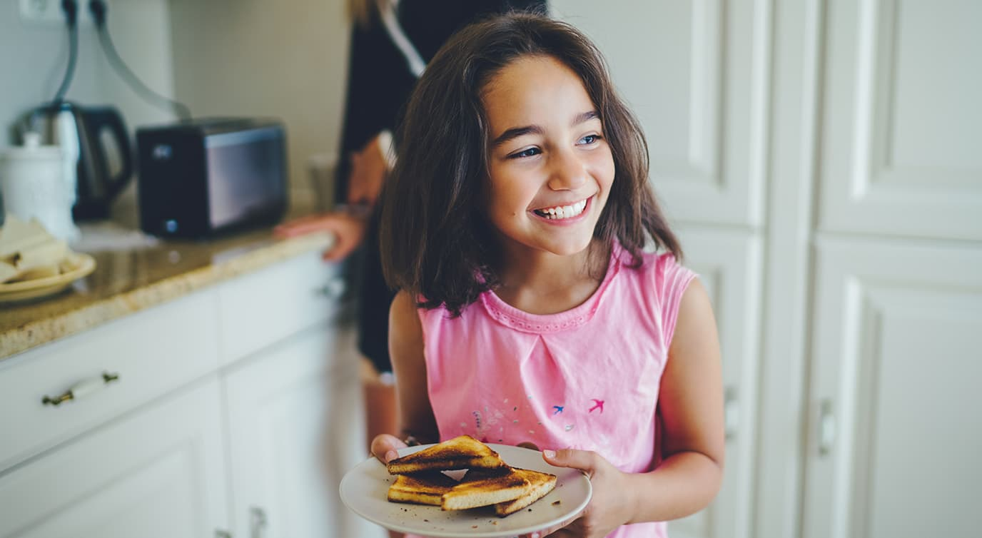 Little girl holding a plate of grilled cheese
