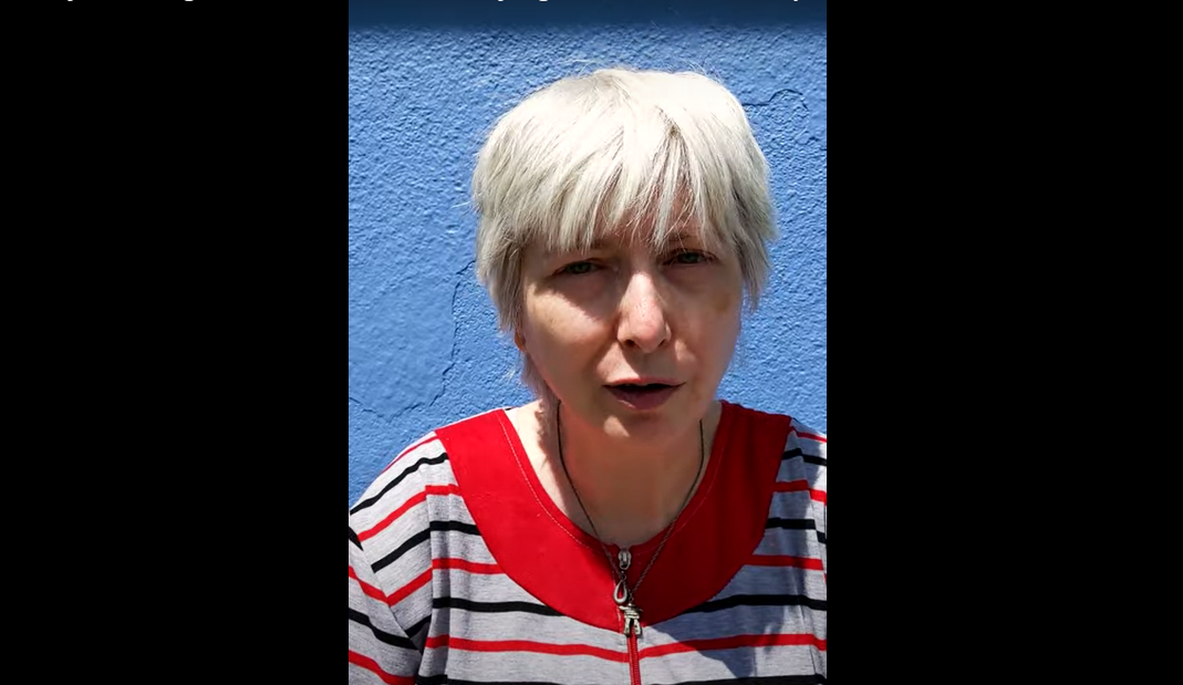 Headshot of an older white woman with short grey hair wearing a striped shirt