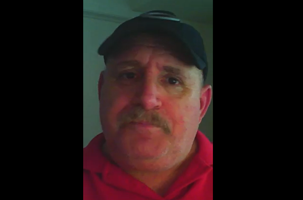 A headshot of a man wearing a baseball cap and a red collared shirt
