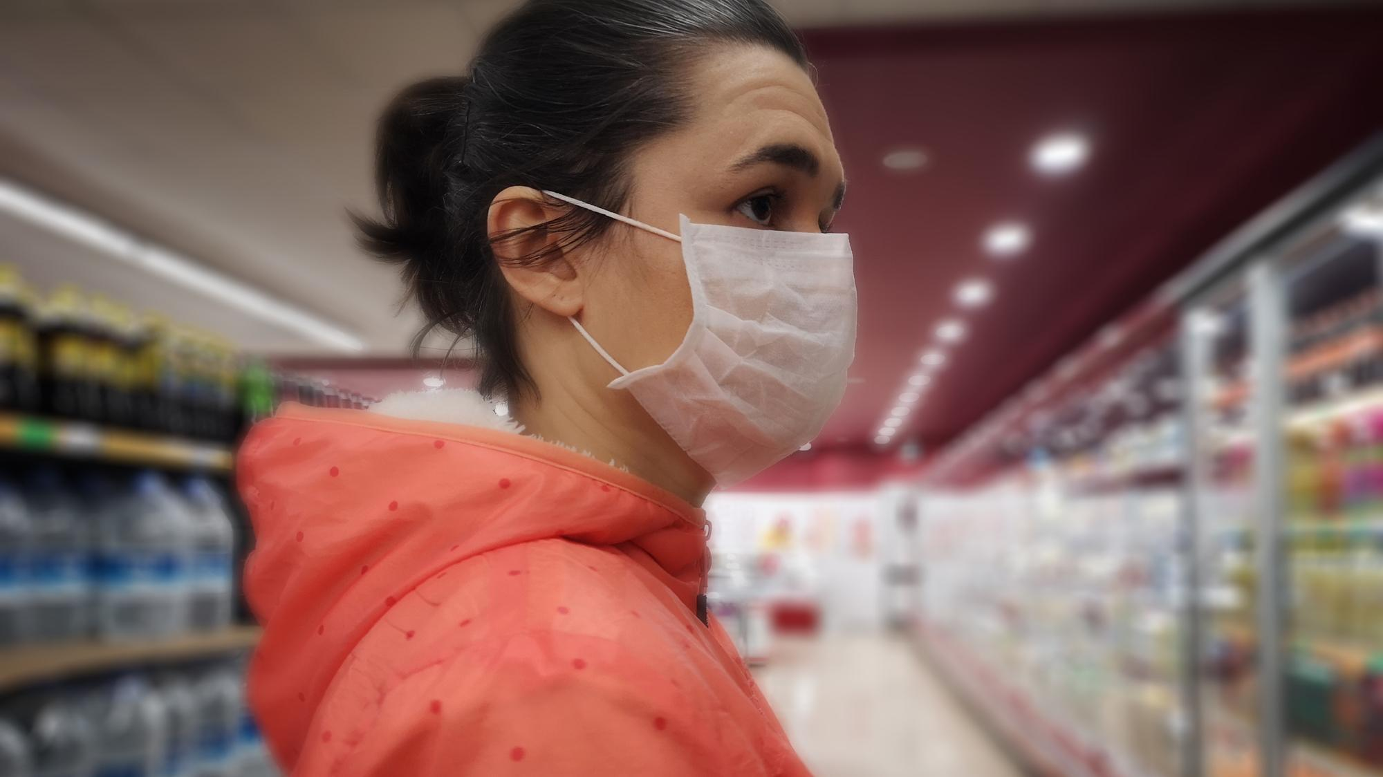 Young woman wears medical mask against virus while grocery shopping in supermarket,  health, safety and pandemic concept